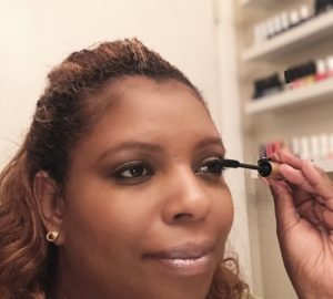 black woman applying L'oreal mascara