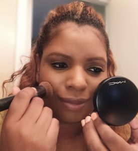black women applying MAC mineralize skin finishing dark